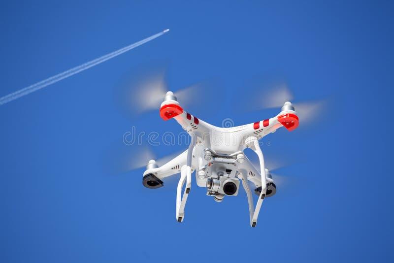 ¿Puede el dron poner en peligro el avión? Abejón y aeroplano junto en el cielo imagen de archivo libre de regalías