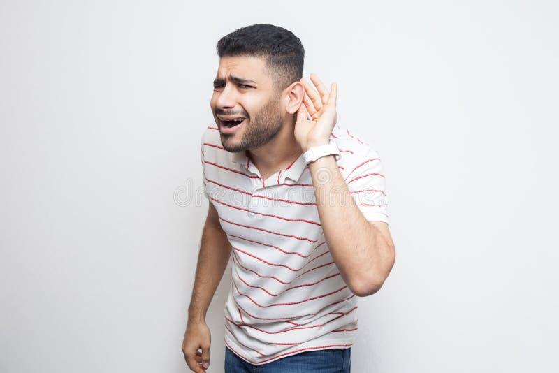¿Qué? No puedo oírle Retrato del hombre joven barbudo hermoso atento en la situación rayada de la camiseta con la mano en el oído imagen de archivo