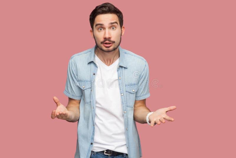 ¿Qué usted quiere? Retrato del hombre joven barbudo hermoso chocado enojado en la camisa azul del estilo sport que coloca y que m imagen de archivo libre de regalías