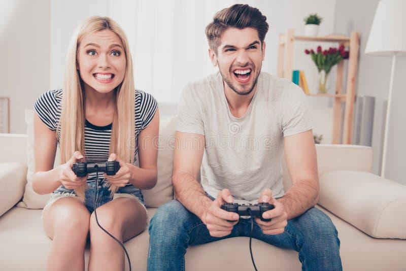 ¿Quién ganará? Los amigos divertidos emocionados están jugando a los videojuegos en imagen de archivo