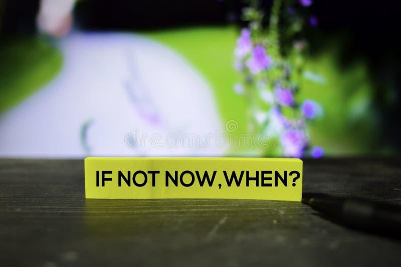 ¿Si no ahora, cuándo? en las notas pegajosas con el fondo del bokeh foto de archivo