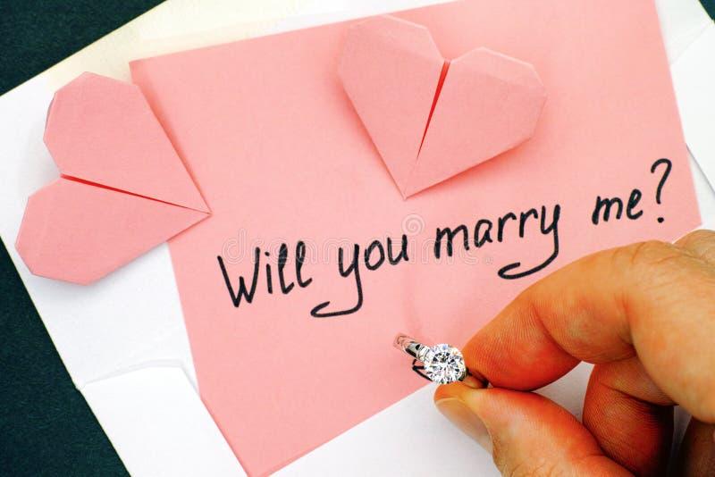 ¿Usted me casará? Mano de la mujer que lleva a cabo el anillo de compromiso imagen de archivo