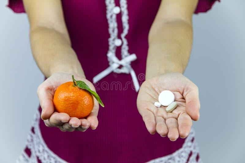 ¿Vitaminas de las frutas o de las medicinas? Una mujer joven en los pijamas de Borgoña muestra un mandarín en su mano derecha y a imagen de archivo libre de regalías