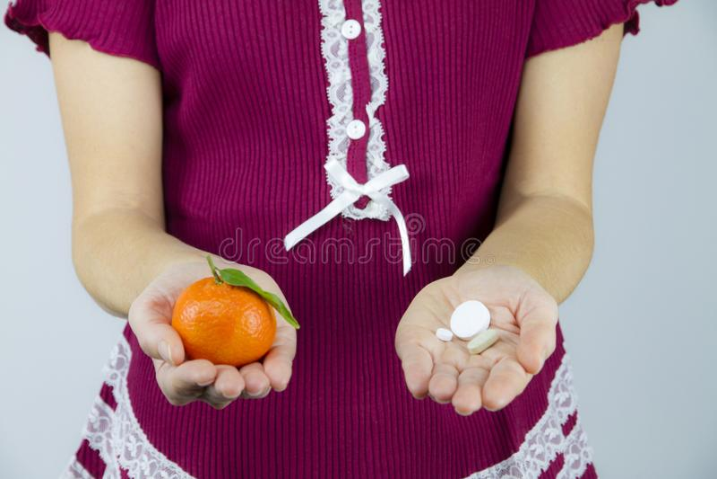 ¿Vitaminas de las frutas o de las medicinas? Una mujer joven en los pijamas de Borgoña muestra un mandarín en su mano derecha y a imagen de archivo