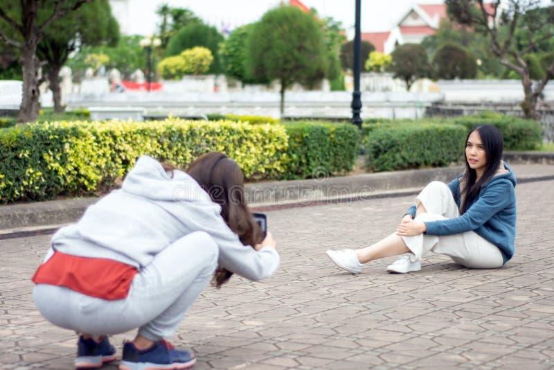 ฺBeautiful asiatisk kvinna med smartphonen som tar bilden av hennes vän i en gammalt stad, livsstil och folkbegrepp arkivbilder