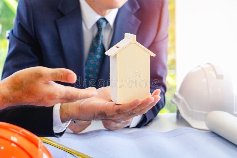 ฺBody part.Business man pointing hand in to modal home. He is present model home for building.They are in office, Spirit, develop ,connection. Photo stock images