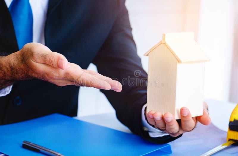 ฺBody part.Business man pointing hand in to modal home. He is present model home for building.They are in office, Spirit, develop ,connection. Photo royalty free stock image