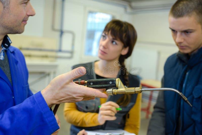 À étudiants de professeur de ferronneries montrant comment utiliser solidement la soudeuse de gaz photos libres de droits