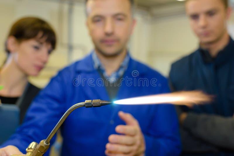 À étudiants de professeur de ferronneries montrant comment utiliser solidement la soudeuse de gaz photo stock