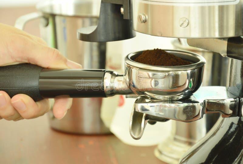 à ¹拿着咖啡粉末的‰手在不锈的杯子射击加工 库存图片