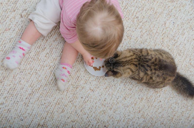 À côté du chat sur le plancher repose un enfant, la fille veut aux honoraires photo libre de droits