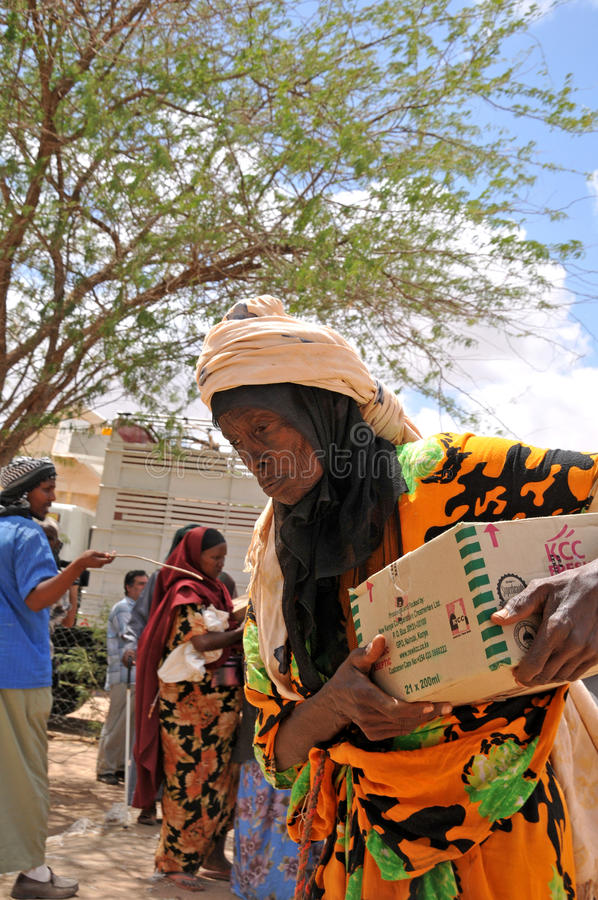À l'aide les Africains après dame âgée retourne à la maison photographie stock