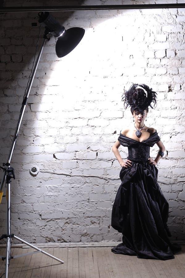 À l'arrière plan de la dame élégante dans la robe noire avec le hairstyl luxueux photo stock