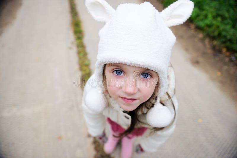 À l'extérieur verticale d'une fille d'enfant dans le chapeau chaud photo libre de droits