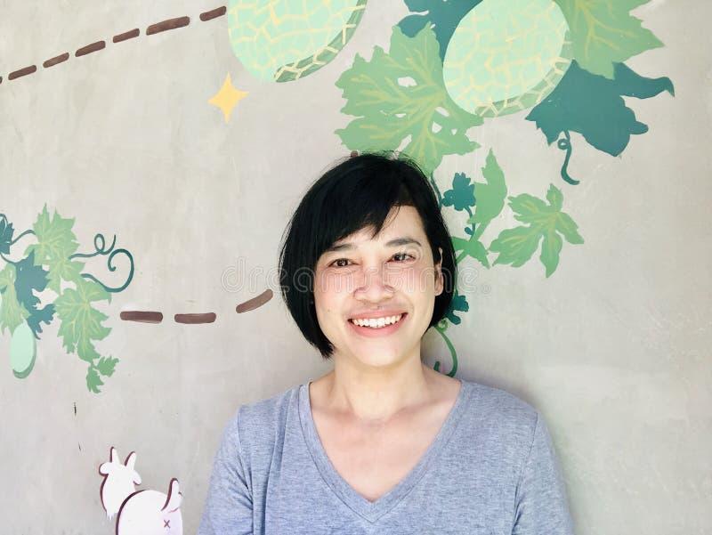 À l'intérieur étroit vers le haut du portrait du sourire de fille ou de la femme asiatique souriant et regardant la caméra images stock