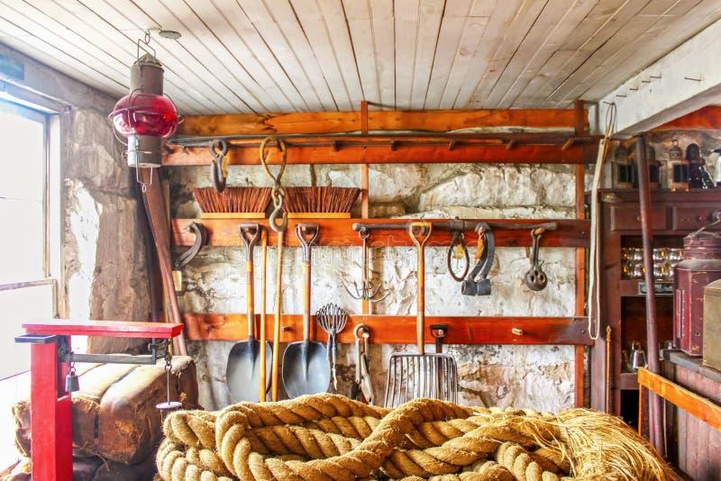 À l'intérieur d'un hangar d'outil avec la corde enroulée dans le premier plan et d'un grand choix d'outils rustiques accrochant s photos stock