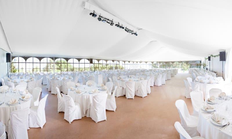 À l'intérieur du grand mariage une tente a installé pour une réception avec des rangées des tables photos stock