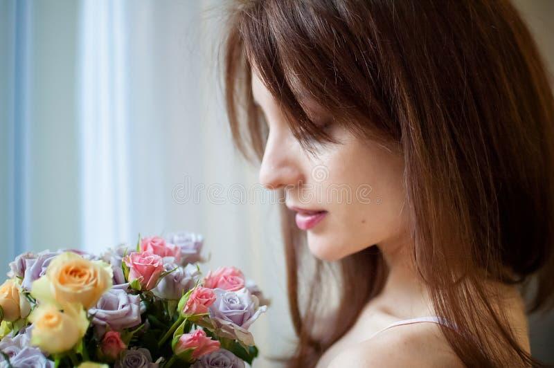 À l'intérieur portrait de la belle position de femme de brune près de la fenêtre avec un bouquet des fleurs appréciant l'odeur photos libres de droits