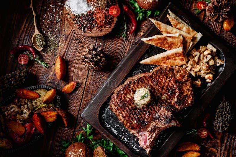 À l'os grillé juteux de bifteck sur le conseil foncé avec les champignons et le pain pita frit image libre de droits