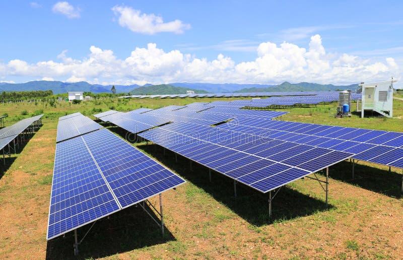 À la ferme solaire moulue sous la montagne Backgrou de ciel bleu et nuageux photos libres de droits
