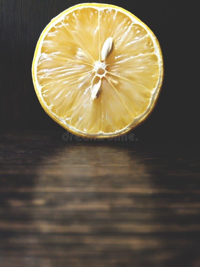 À moitié un citron se trouve sur une obscurité photos stock