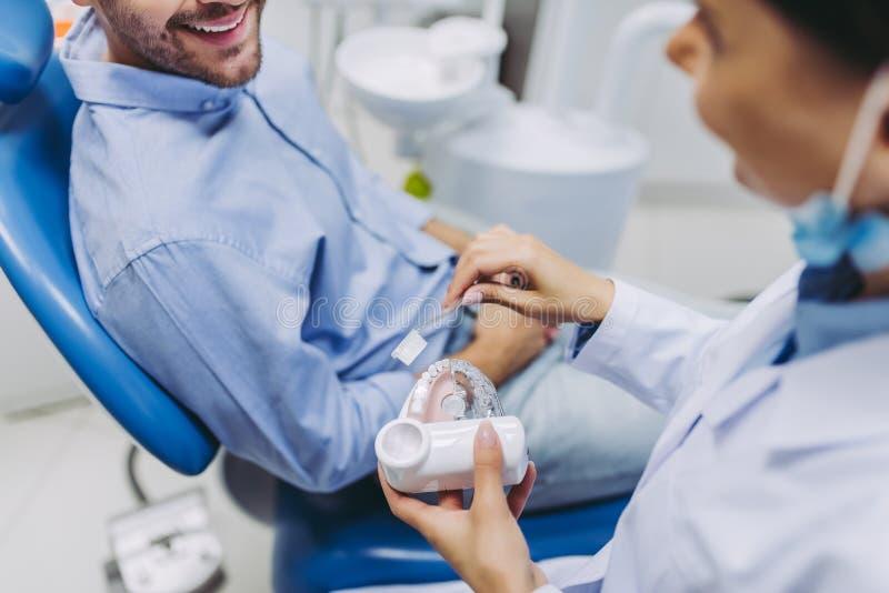 À patient de dentiste en montrant comment brosser des dents sur des mâchoires modelez photographie stock libre de droits