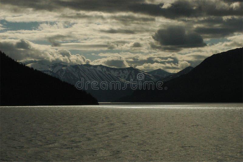 à travers les montagnes foncées de lac photographie stock