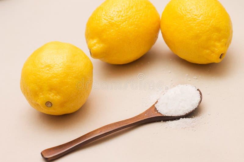 Ácido cítrico en una cuchara de madera y limones foto de archivo libre de regalías