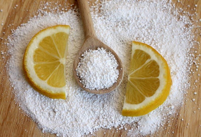 Ácido cítrico na colher de madeira com limão imagem de stock royalty free