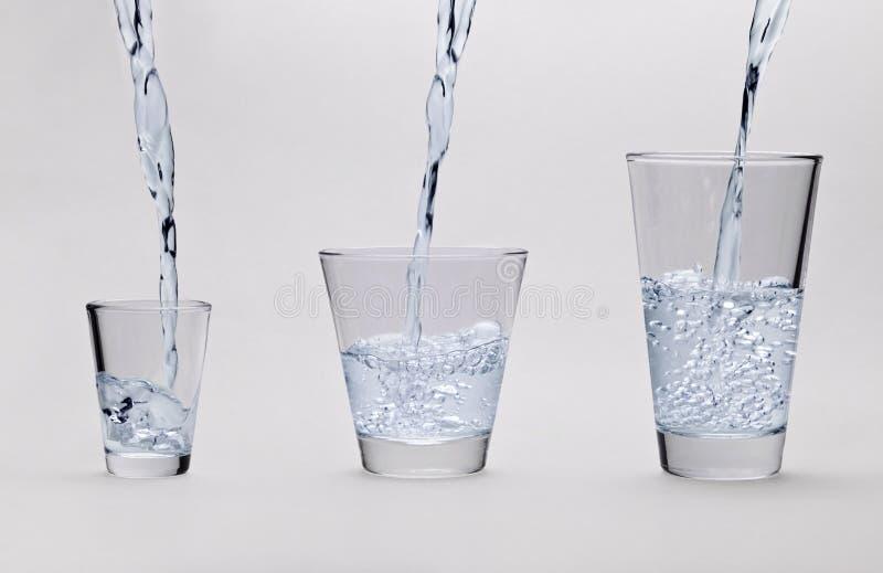 A água é derramada em três vidros fotos de stock royalty free