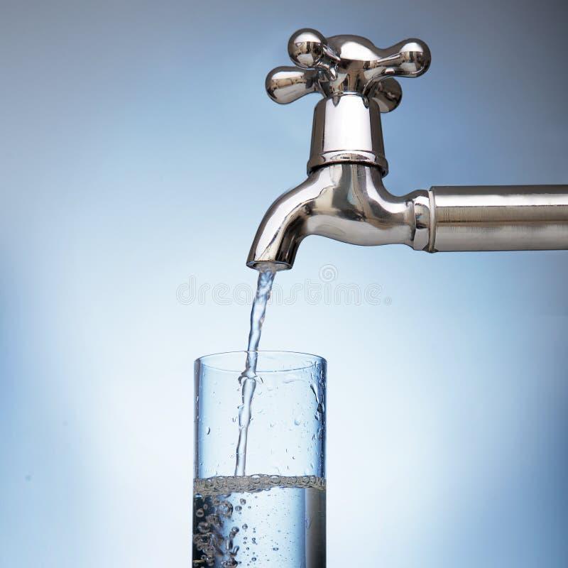 A água é derramada em um vidro da torneira imagens de stock royalty free