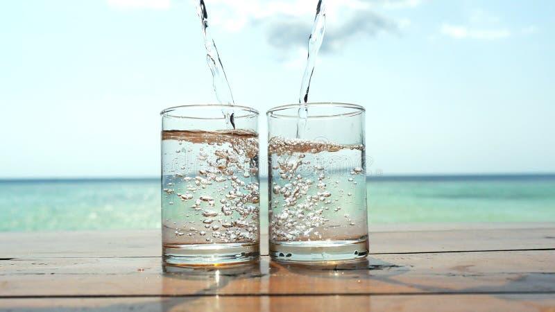 A água é derramada em uns vidros contra o mar em uma praia tropical foto de stock