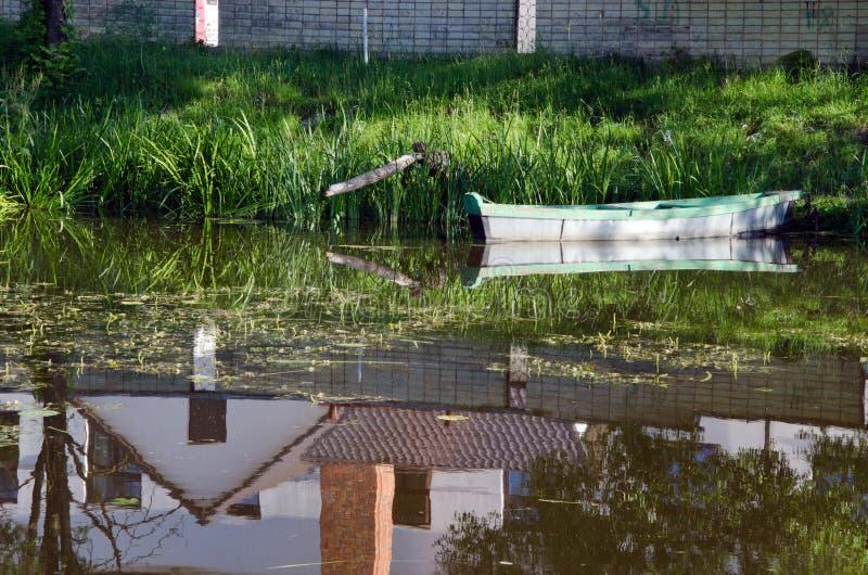 Água amarrada barco das reflexões da casa da costa do rio imagens de stock royalty free