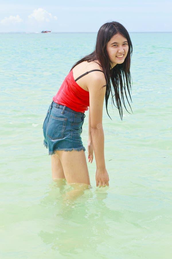 Água asiática bonita do jogo da mulher no mar foto de stock