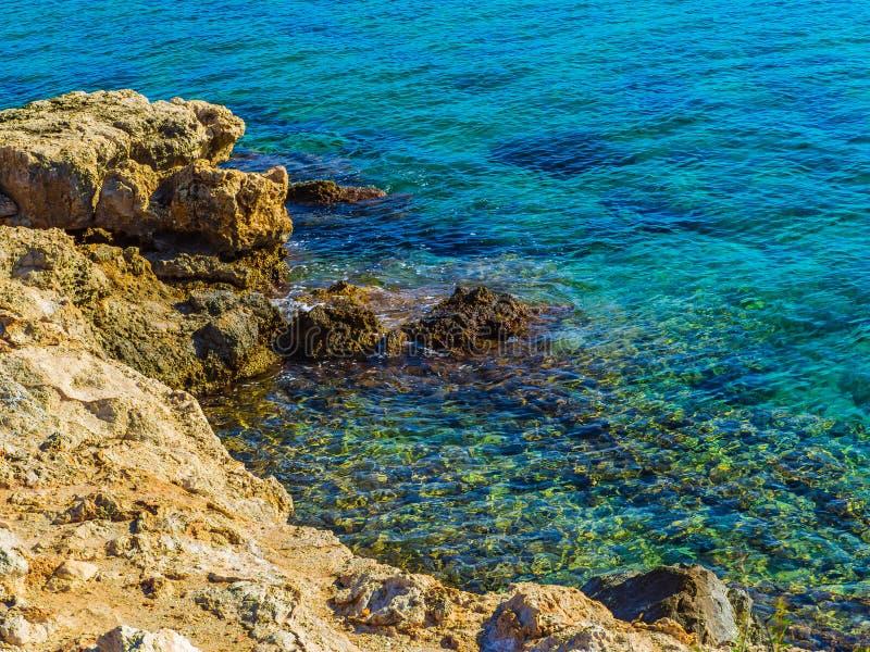?gua azul claro de surpresa e bordas afiadas da rocha na costa imagem de stock