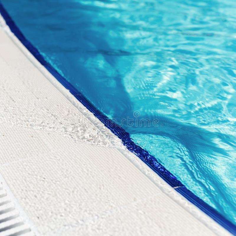 Água azul com reflexão clara na borda da piscina curvada imagens de stock royalty free