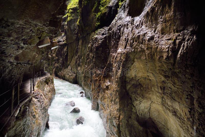 Água azul que flui no desfiladeiro ou no Partnachklamm de Partnach, entalhado por um córrego da montanha no vale de Reintal perto imagens de stock