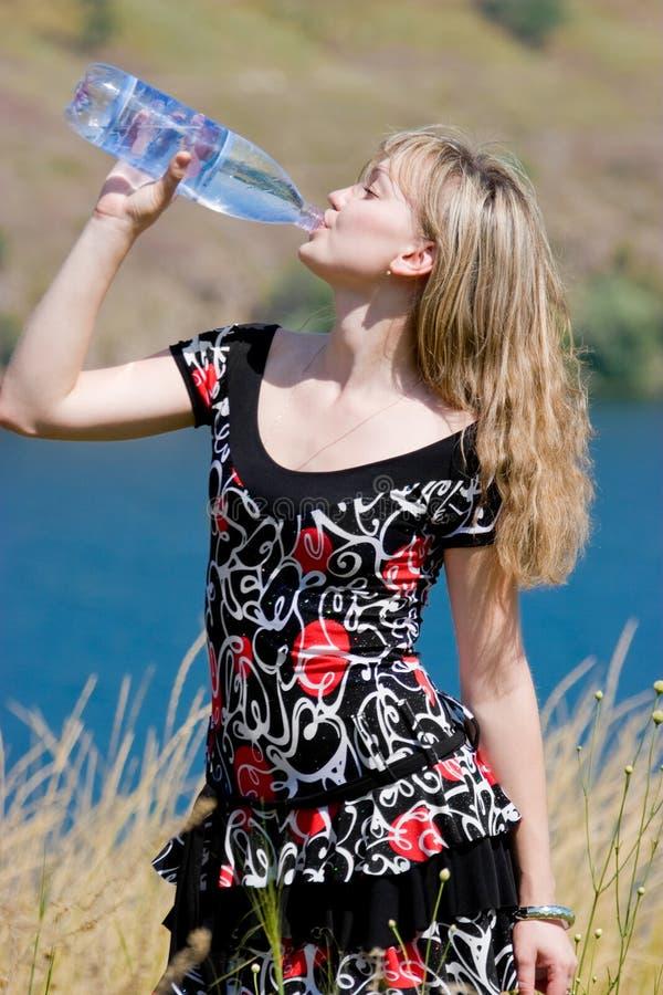 Água bebendo da rapariga do frasco plástico foto de stock