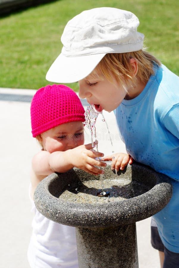 Água bebendo das crianças em uma fonte bebendo foto de stock