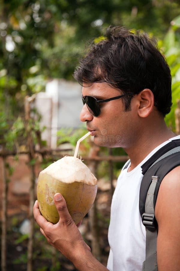 Água bebendo do coco do homem indiano feliz foto de stock