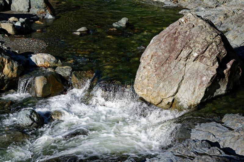 Água branca devido a um pedregulho que altera o fluxo do rio fotografia de stock