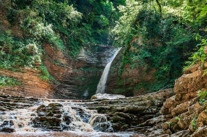 A água cai de um penhasco e flui belamente sobre as rochas imagem de stock royalty free