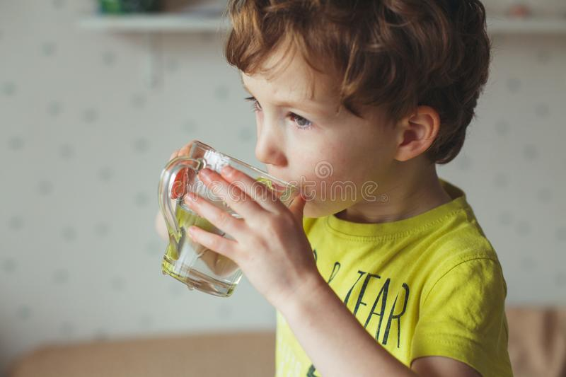 Água caucasiano pequena da bebida do menino no vidro em casa A criança encaracolado bonito é água potável Saúde e conceito da águ imagens de stock royalty free