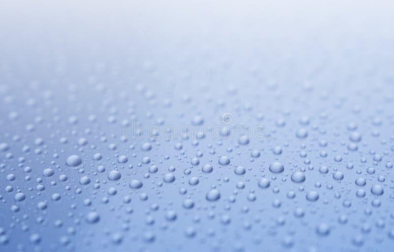 A água clara deixa cair na luz do inclinação - fundo azul imagem de stock
