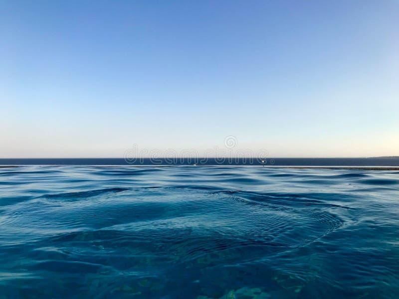 A água clara natural dos azuis celestes molhados azuis bonitos contra um céu azul e o horizonte alinham em um recurso morno tropi foto de stock royalty free