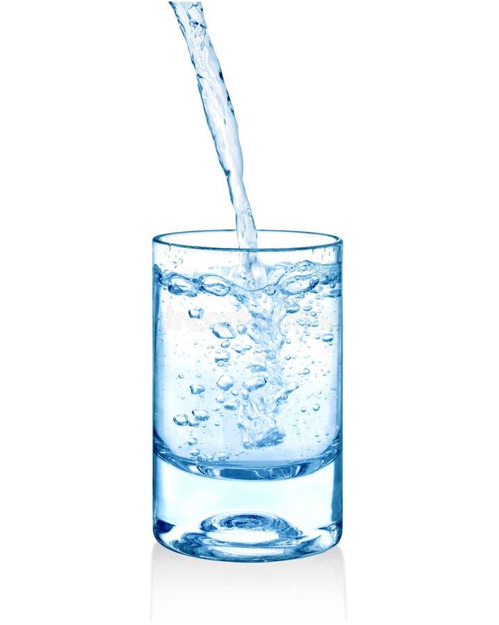 Água clara que está sendo derramada em um copo de vidro isolado fotografia de stock
