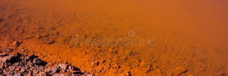 Água contaminada e solo com os óxidos de ferro na zona industrial Bandeira para o projeto imagens de stock