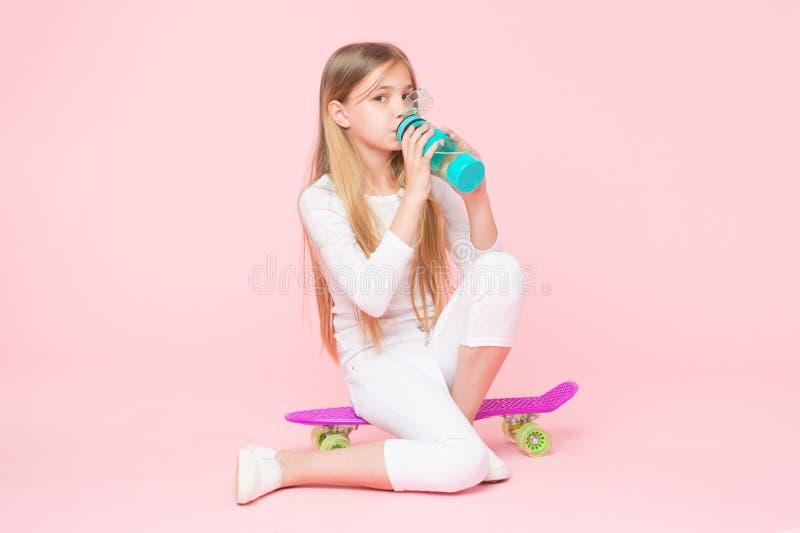 A água dá sua energia Água potável do skater da menina no fundo cor-de-rosa Criança sedento que bebe a água fresca de imagens de stock royalty free