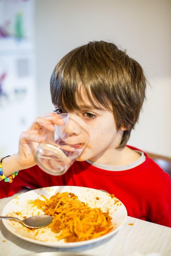 Água da bebida da criança e espaguetes comer foto de stock