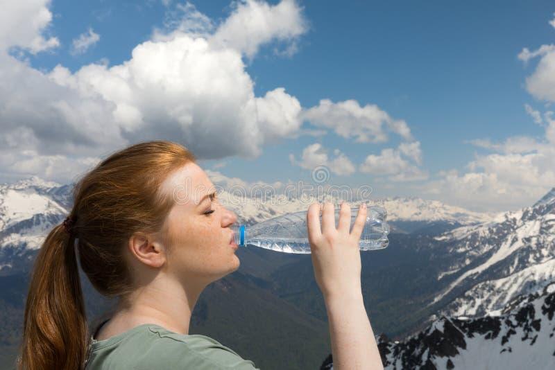 A água da bebida da jovem mulher da garrafa plástica nas montanhas na neve repica o fundo fotos de stock royalty free